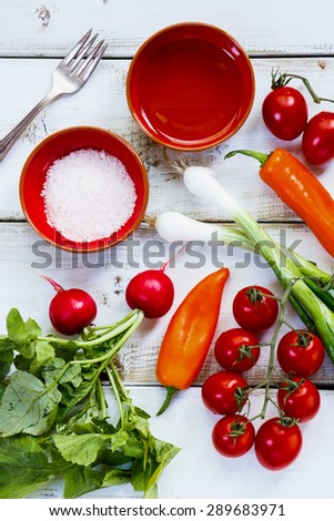 Fresh Ingredients of vegetable salad on white wooden background. Healthy or vegetarian eating concept. - stock photo