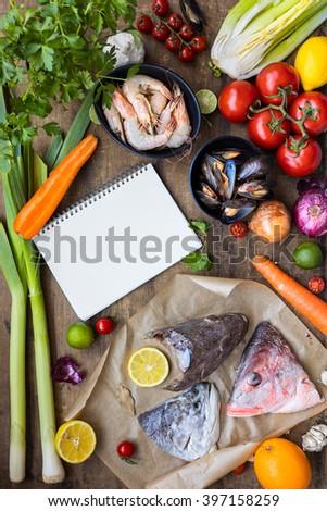 Fresh ingredients to cook fish soup, bouillabaisse: fish heads, onion, lime, lemon, leak, parsley, tomatos, carrot, celery, mussels, shrimps. Top view - stock photo