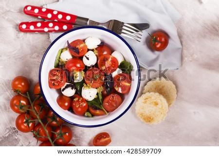 Fresh italian caprese salad  mozzarella, cherry tomatoes and pesto sauce in enamel bowl. Selective focus. Toned image. Top view - stock photo