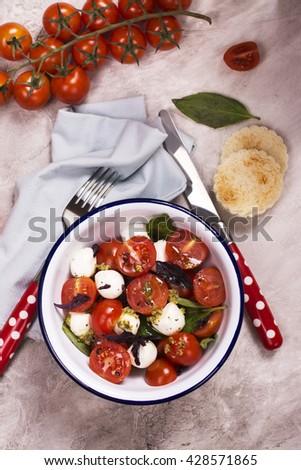 Fresh italian caprese salad  mozzarella, cherry tomatoes and pesto sauce in enamel bowl. Top view. Selective focus - stock photo