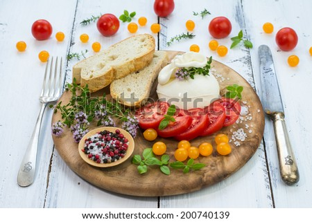 Fresh italian cheese burrata on a vintage plate with assorted tomatoes and basil on a painted wooden surface - stock photo