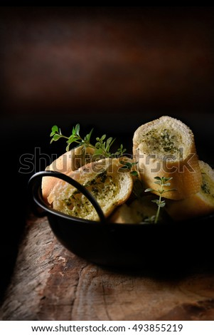 Fresh Italian garlic sliced baguette bread roll ready for serving against a rustic background seasoned with fresh thyme herbs. The perfect image for your rustic menu cover design art. Copy space.