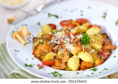 Fresh Italian gnocchi with fried chanterelles, tomatoes, bacon and parmesan cream sauce - stock photo