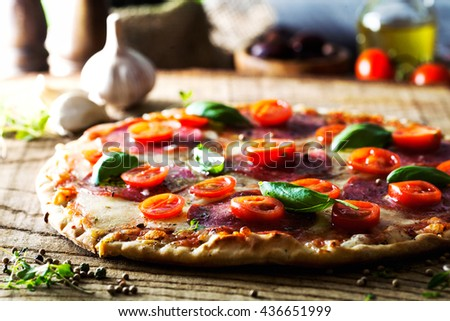 Fresh italian  pizza on wood. Pizza with cheese, salami and tomatoes. Fast food. Rustic pizza - stock photo