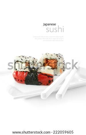 Fresh Japanese Sushi cuisine against a white background with chop sticks. Copy space. - stock photo