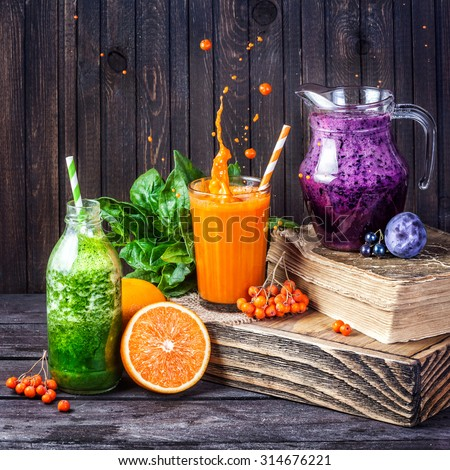Fresh juice and smoothies with berries, fruits and green spinach on wooden background   - stock photo