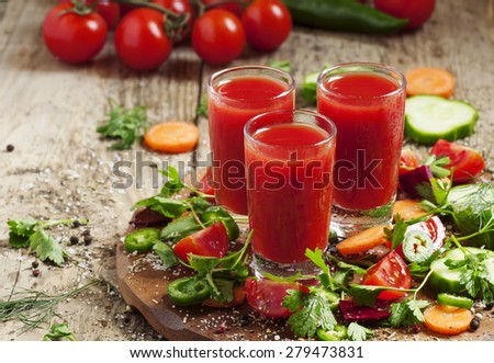 Fresh juice from the mix of vegetables with vegetables and herbs on a wooden table, selective focus - stock photo
