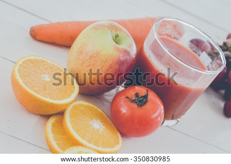 Fresh juice glass and fruits on table - healthy eating - stock photo