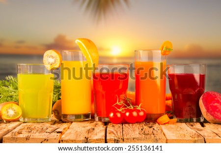 Fresh juice, mix fruits and vegetable on wooden table with sunset background. - stock photo