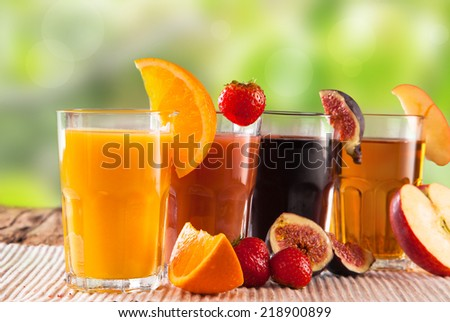 Fresh juice, mix fruits orange, strawberry, lime, apple and ficus drinks with nature background.  - stock photo