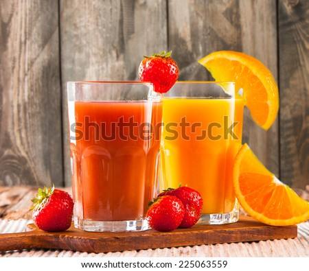 Fresh juice, mix fruits, strawberry and orange drinks on wood plants  - stock photo