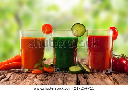 fresh juice, mix vegetable, carrot, tomato and cucumber drinks with nature green background  - stock photo