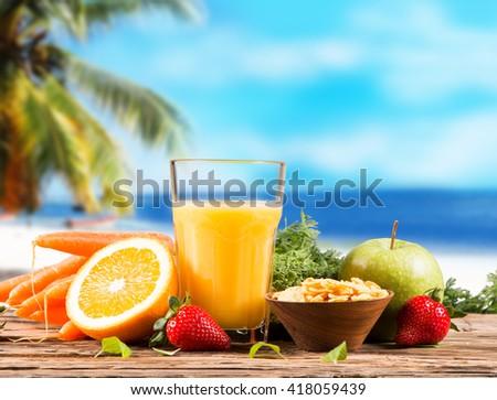 Fresh juice orange on wood with tropical beach background - stock photo