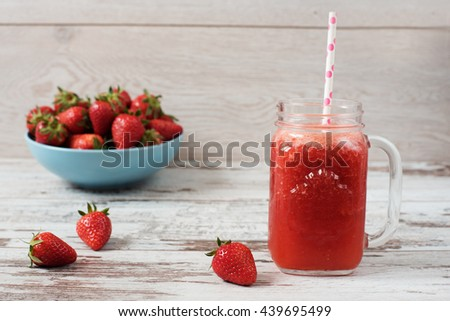 Fresh juice, shake, milkshake of strawberries in a mason jar with a straw. Pile of juicy ripe organic fresh strawberries in a large blue bowl. Light rustic wooden background - stock photo