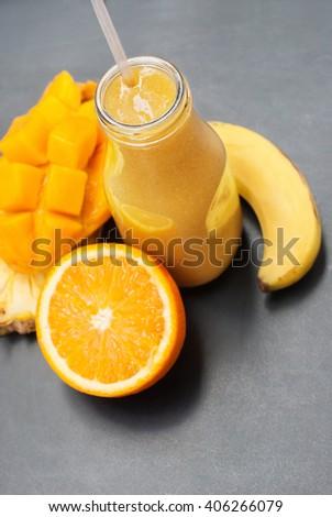 Fresh Juice Smoothie Glass Bottle Yellow Fruits Orange Banana Mango Pine apple Vitamin Diet Healthy Concept Black Background - stock photo