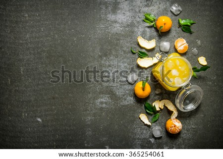 Fresh juice with mandarins, leaves, and ice. On a stone background. Free space for text . Top view - stock photo