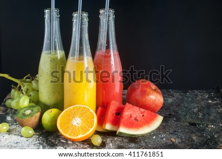 Fresh Juices Smoothie Tall Bottles Yellow Red Green Tropical Colorful Fruits Water Melon Apple Kiwi Grape Orange Mango Black Background Selective focus - stock photo