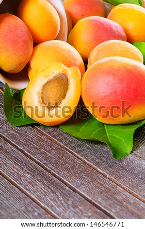 Fresh juicy apricots scattered on the wooden background - stock photo