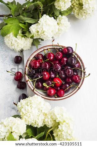 Fresh juicy cherries bowl and white flowers - stock photo