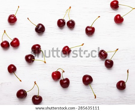 Fresh juicy cherries on the white wooden background, top view - stock photo