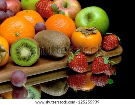fresh juicy fruits and berries on a black background with reflection closeup - stock photo