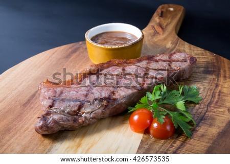 Fresh juicy grilled beef steak on wooden board - stock photo