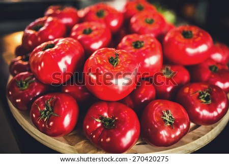 Fresh juicy italian tomatoes on wooden board just collected in garden and ready for being cooked - stock photo