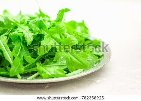 Fresh juicy leaves of arugula on a light concrete background