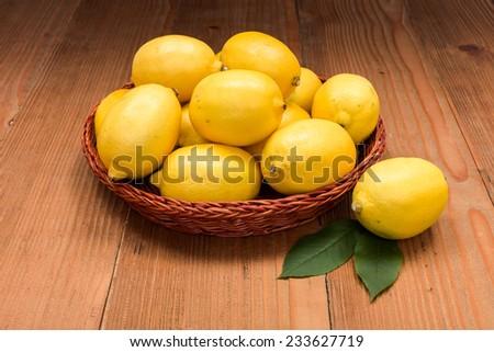 Fresh juicy lemons in wooden tray on board - stock photo