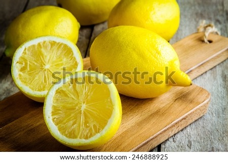 Fresh juicy lemons on a cutting board on a rustic wooden background - stock photo