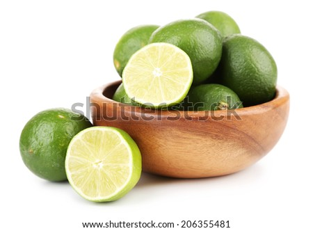 Fresh juicy limes in wooden bowl, isolated on white - stock photo