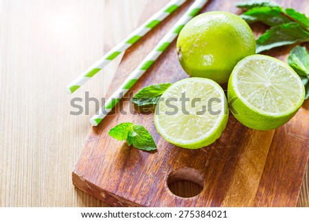 Fresh juicy limes, mint leaves and a cocktail stick on a wooden cutting board - stock photo