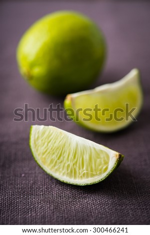 Fresh juicy limes on dark canvas background close up - stock photo
