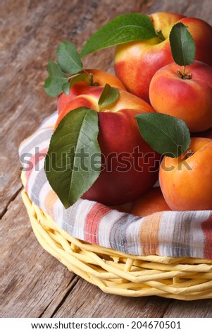 Fresh juicy nectarine, peaches and apricots in a basket closeup vertical  - stock photo