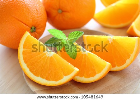 Fresh juicy oranges with mint leaves on  wooden plate - stock photo