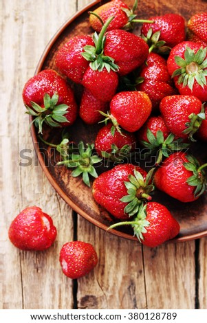 fresh juicy organic strawberries in an old clay bowl - stock photo