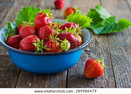fresh juicy organic strawberries in an old metal bowl on a wooden background - stock photo