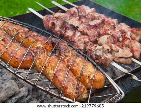 Fresh juicy shashlik and fish  on the grill.  - stock photo