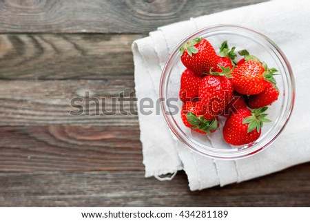 Fresh juicy strawberries in glass bowl. Rustic background with homespun napkin. Top view. Place for text. - stock photo