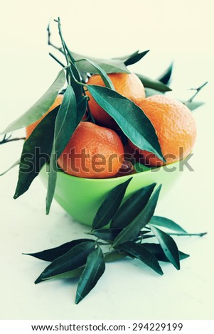Fresh juicy tangerines in a green bowl - stock photo