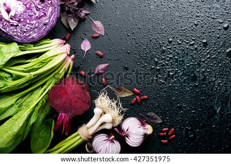 Fresh juicy vegetables such as  basil, beets, young peas, green pepper, garlic and spinach on black background. Vegan concept.  Place for writing text. Vegetable background - stock photo