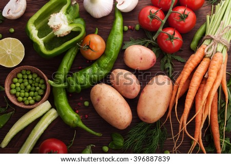 Fresh juicy vegetables such as carrots, peas, tomatoes, green peppers and potatoes on brown wooden board. Vegetarian concept.