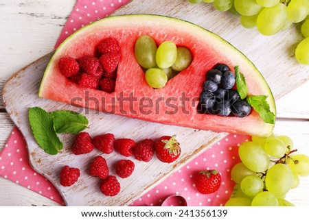 Fresh juicy watermelon slice  with cut out heart shape, filled fresh berries, on cutting board, on wooden background - stock photo