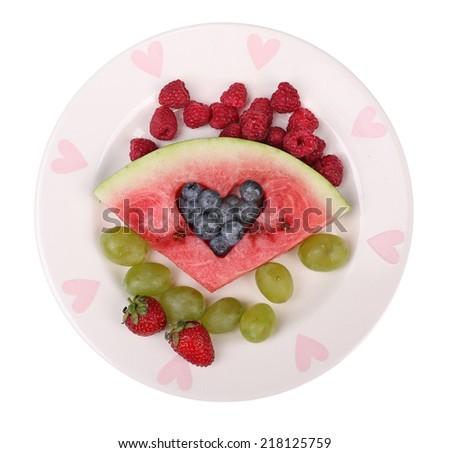 Fresh juicy watermelon slice  with cut out heart shape, filled fresh berries, on plate, isolated on white - stock photo