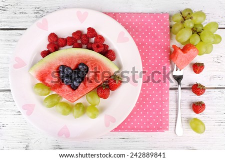 Fresh juicy watermelon slice  with cut out heart shape, filled fresh berries, on plate, on wooden background - stock photo