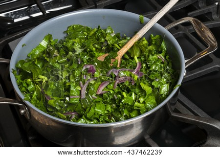 Fresh kale sauteed with onions in a cooking pan on gas stove