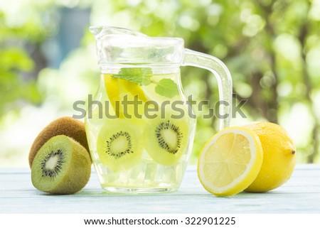 Fresh kiwi and lemon juice  on wooden table;  healthy drink. - stock photo