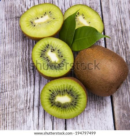 Fresh kiwi fruits on wooden table. Wood background. - stock photo