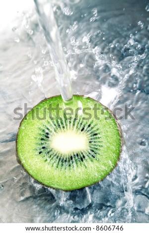 Fresh kiwi jumping into water - stock photo