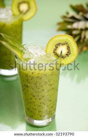 Fresh kiwi smoothie over green background - stock photo